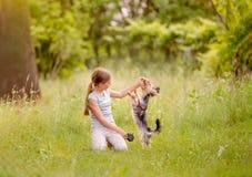 Niña que juega con el perro del terrier Fotos de archivo libres de regalías
