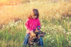 Niña que juega con el perro en el prado imagen de archivo libre de regalías