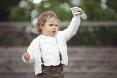 Niña que juega con el teléfono móvil Imagen de archivo libre de regalías