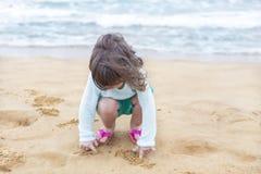 Niña que juega con la arena en la playa Imágenes de archivo libres de regalías