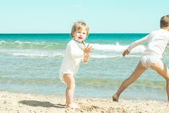 Niña que juega con la arena en la playa fotos de archivo