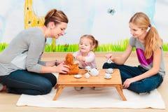 Niña que juega con la mamá y la hermana en la fiesta del té que usa al niño Fotos de archivo