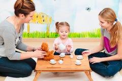 Niña que juega con la mamá y la hermana en la fiesta del té que usa al niño Foto de archivo libre de regalías