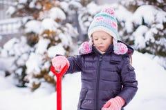 Niña que juega con la pala roja en el jardín Foto de archivo libre de regalías