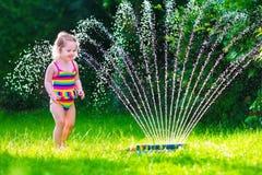 Niña que juega con la regadera del agua del jardín Imagen de archivo