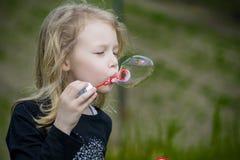 Niña que juega con las burbujas de jabón Foto de archivo