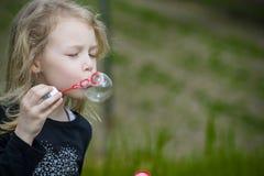 Niña que juega con las burbujas de jabón Fotografía de archivo libre de regalías