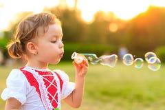Burbujas de jabón del niño que soplan. imagenes de archivo