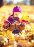 Niña que juega con las hojas de otoño Imagenes de archivo