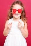 Niña que juega con los corazones de las tarjetas del día de San Valentín Foto de archivo
