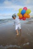 Niña que juega con los globos en la playa Fotos de archivo