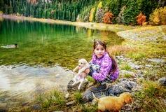 Niña que juega con los perros en la costa del th del lago negro (Cr Foto de archivo libre de regalías