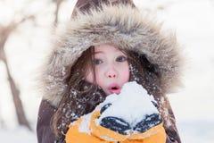 Niña que juega con nieve en invierno Foto de archivo libre de regalías