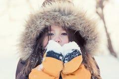 Niña que juega con nieve en invierno Imagen de archivo libre de regalías