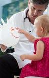 Niña que juega con su pediatra Fotografía de archivo