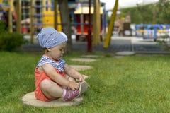 Niña que juega con sus sandalias que se sientan en la hierba verde fotografía de archivo