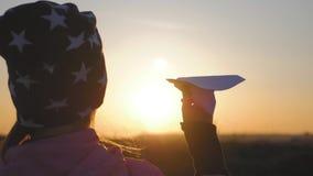 Niña que juega con un aeroplano de papel Concepto de sueños y de viaje metrajes