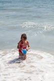 Niña que juega con un compartimiento en la playa foto de archivo
