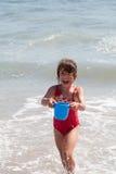 Niña que juega con un compartimiento en la playa fotografía de archivo