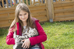 Niña que juega con un gato Imagen de archivo libre de regalías