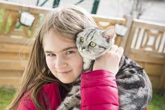 Niña que juega con un gato Foto de archivo