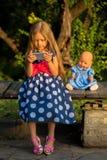 Niña que juega con un smartphone al aire libre Imagen de archivo libre de regalías