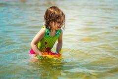Niña que juega con una bola colorida en el mar Foto de archivo libre de regalías