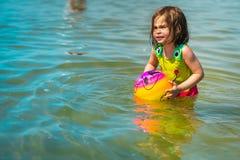 Niña que juega con una bola colorida en el mar Fotos de archivo libres de regalías