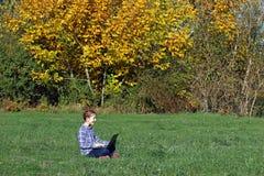 Niña que juega el ordenador portátil en la estación del otoño del parque Fotografía de archivo