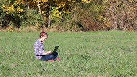 Niña que juega el ordenador portátil en la estación del otoño del parque almacen de video
