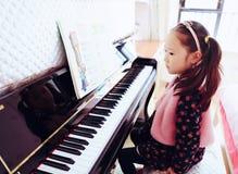 Niña que juega el piano en casa Imagen de archivo libre de regalías