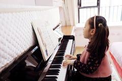 Niña que juega el piano en casa Foto de archivo libre de regalías
