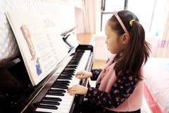 Niña que juega el piano en casa Fotografía de archivo libre de regalías