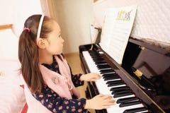 Niña que juega el piano en casa Imagenes de archivo