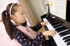 Niña que juega el piano en casa Fotos de archivo libres de regalías