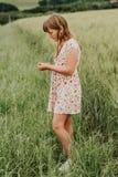 Niña que juega en campo de trigo verde en verano Foto de archivo