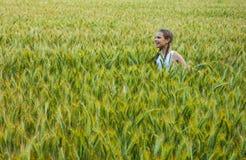 Niña que juega en el campo de trigo en un día de verano caliente Fotos de archivo