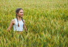 Niña que juega en el campo de trigo en un día de verano caliente Fotos de archivo libres de regalías