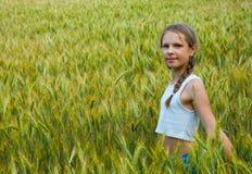 Niña que juega en el campo de trigo en un día de verano caliente Imágenes de archivo libres de regalías