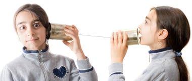 Niña que juega en el teléfono construido con el tarro Foto de archivo