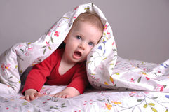 Niña que juega en la cama Foto de archivo libre de regalías