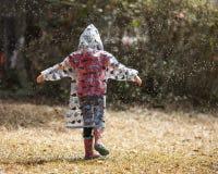 Niña que juega en la lluvia Imagen de archivo libre de regalías