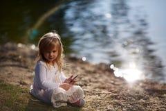 Niña que juega en la orilla del río Foto de archivo libre de regalías