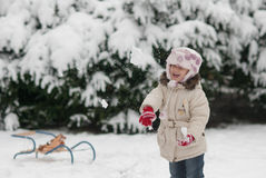 Niña que juega en las bolas de nieve de la nieve y del tiro Imagen de archivo