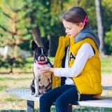 Niña que juega en un parque del otoño con el perro del terrier de Boston L foto de archivo