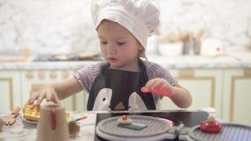 Niña que juega en una cocina de los niños de madera elegantes almacen de metraje de vídeo