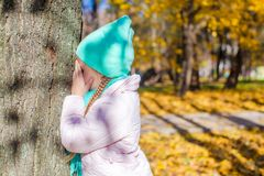 Niña que juega escondite cerca del árbol adentro Fotos de archivo