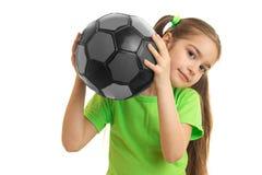 Niña que juega a fútbol en balón de fútbol Fotografía de archivo