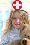 Niña que juega a la enfermera con el oso Foto de archivo libre de regalías