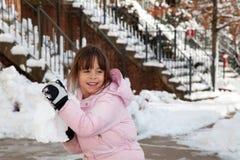 Niña que lanza una bola gigante de la nieve foto de archivo